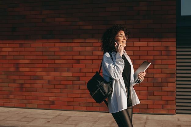 Charmante blanke student die enkele boeken vasthoudt en een telefoongesprek voert tijdens een zomerse wandeling