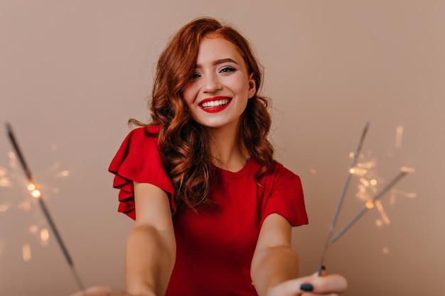 Charmante blanke vrouw in rode jurk met bengalen lichten. aanbiddelijk meisje dat nieuw jaar met glimlach viert.