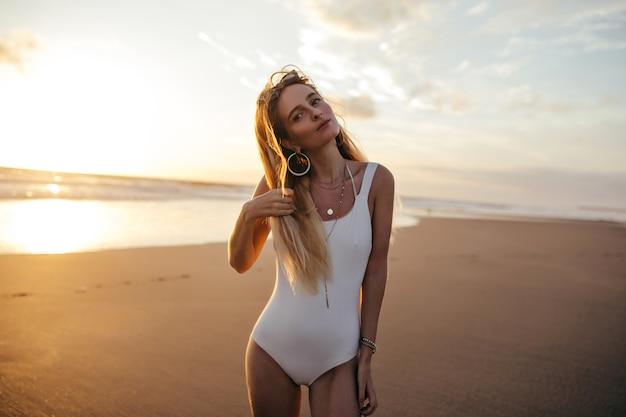 Charmante blanke vrouw in trendy oorbellen poseren aan zandstrand in vakantie.
