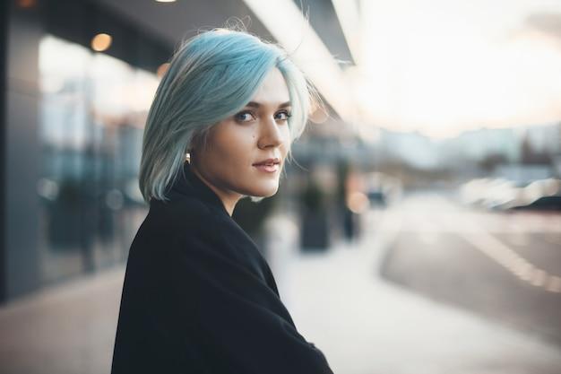Charmante blanke vrouw met blauw haar die naar voren kijkt terwijl ze buiten op straat juicht