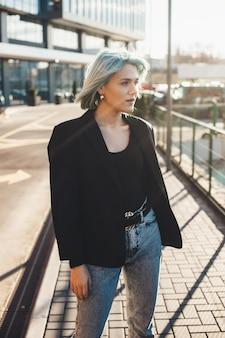 Charmante blanke vrouw met blauw haar poseren buiten in de straat wegkijken tegen de zon