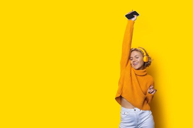 Charmante blanke vrouw met blond haar luistert naar muziek en danst op een gele muur met vrije ruimte