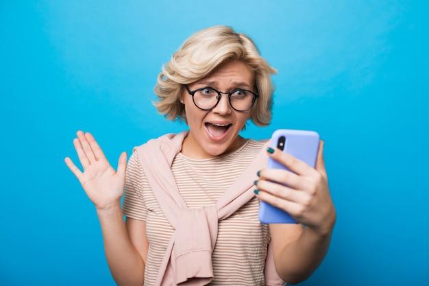 Charmante blanke vrouw met blond haar staat versteld van iets terwijl ze een telefoon vasthoudt en poseren op een blauwe achtergrond