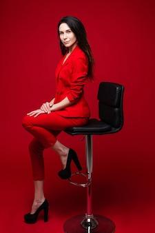 Charmante blanke vrouw met lang donker steil haar in een rood kantoorpak, zwarte schoenen zit op een zwarte stoel en poseert voor de camera