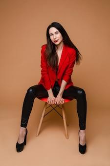 Charmante blanke vrouw met lang donker steil haar in rood en zwart kantoorpak, zwarte schoenen zit op rode stoel