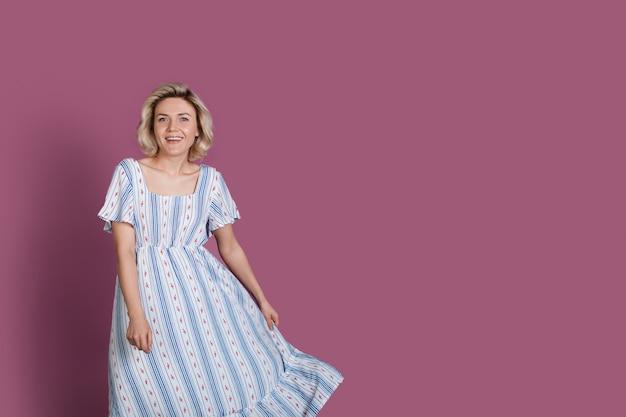 Charmante blonde blanke vrouw lachend op een violette studiomuur met vrije ruimte terwijl ze een zomerjurk draagt
