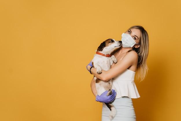Charmante blonde in chirurgisch masker en beschermende handschoenen, gekleed in een lichte blouse en rok omhelst haar hond, zorgt voor vrienden tijdens quarantaine vanwege coronavirus pandemie. covid-19 concept.