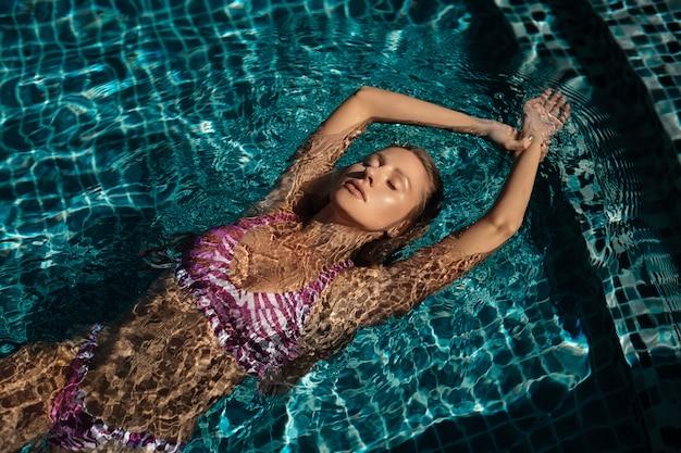 Charmante blonde in een roze badpak zwemt in het zwembad. luxe vakantieschoten