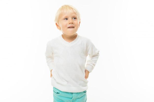 Charmante blonde jongen in een wit t-shirt denken op een witte muur