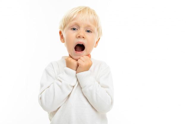 Charmante blonde jongen in een wit t-shirt toont een grimas op een witte muur