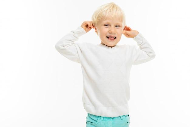Charmante blonde jongen in een wit t-shirt trekt zich aan de oren op een witte muur