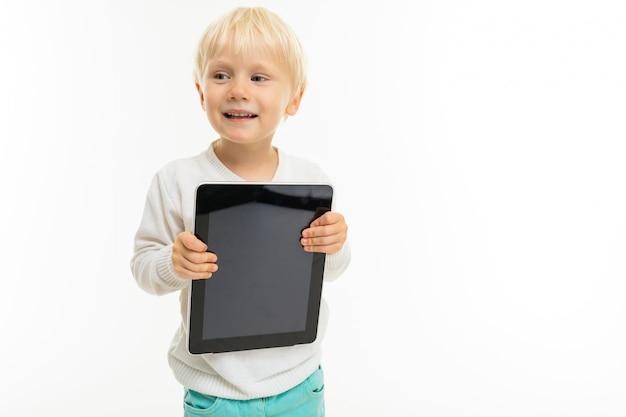 Charmante blonde jongen met een tablet op een witte muur