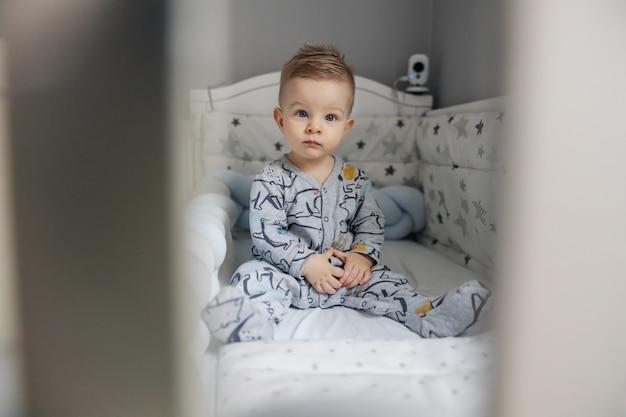Charmante blonde kleine baby die 's ochtends in zijn wieg zit, met een ernstig gezicht