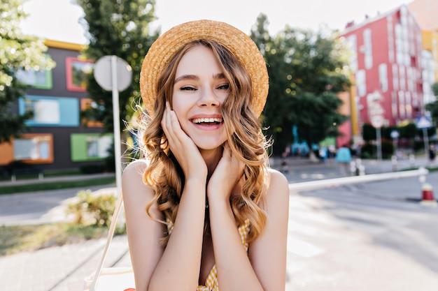 Charmante blonde meisje haar gezicht aan te raken tijdens fotoshoot buiten op straat. blije elegante vrouw die in zonnige dag lacht.