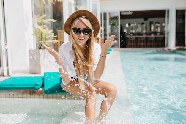 Charmante blonde meisje in zonnebril gek rond tijdens fotoshoot met water. outdoor portret van lachen zorgeloze dame in trendy zomerhoed.