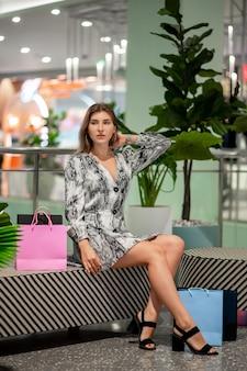 Charmante blonde meisje poseren zittend in een winkel met packs met klanten, kijkt weg en wacht. zwarte vrijdag. uitverkoop. kortingen.