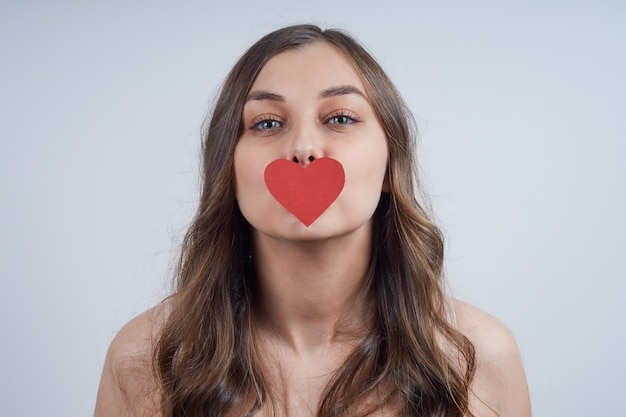Charmante blonde met een papieren hart op haar lippen. fijne valentijnsdag.