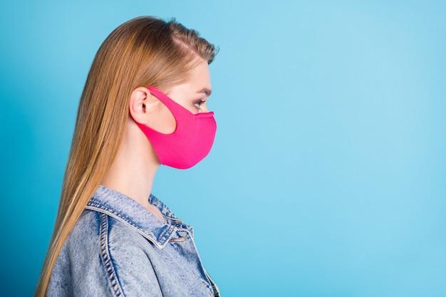 Charmante blonde schattige dame draagt een roze beschermend medisch masker