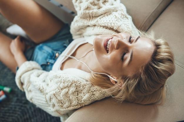 Charmante blonde vrouw is ontspannen op een bank terwijl u naar muziek luistert
