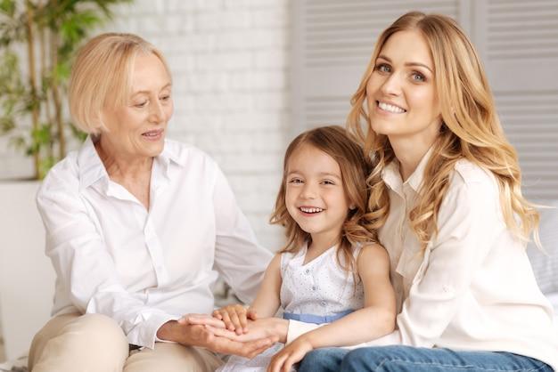 Charmante blonde vrouw omarmen haar lieve dochtertje en hand in hand samen met haar kind en haar moeder kijken naar het meisje met een liefdevolle glimlach
