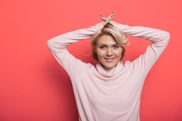 Charmante blonde vrouw op een rode muur lacht naar de camera, hand in hand op het hoofd