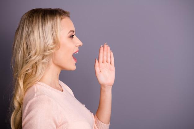 Charmante blonde vrouw poseren tegen de paarse muur