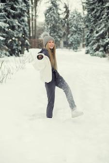 Charmante blonde vrouw spelen met sneeuw in het bos
