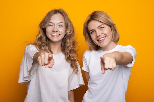Charmante blonde vrouwen die naar voren wijzen