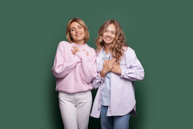 Charmante blonde zussen op een groene muur gebaren dat het hartteken hun borst aanraakt
