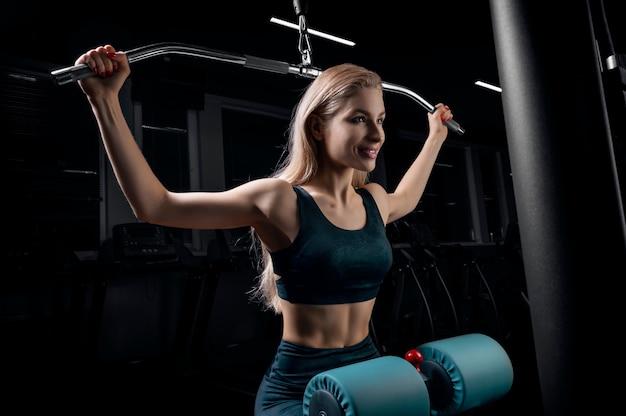 Charmante blondine doet oefeningen voor de rug in de sportschool. nek trekken voor het hoofd. het concept van sport, bodybuilding, fitness. gemengde media