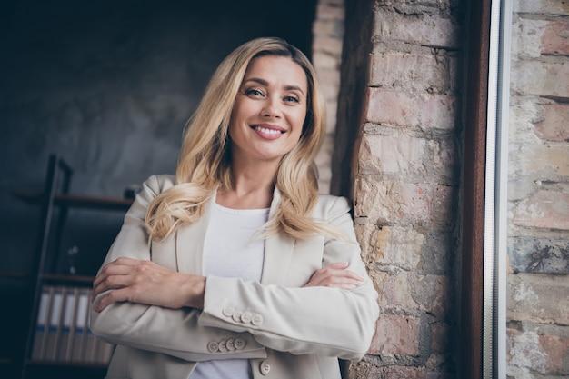 Charmante brede stralende baas dame met gevouwen handen dragen blazer glimlachend in de buurt van raam in kantoor van haar bedrijf
