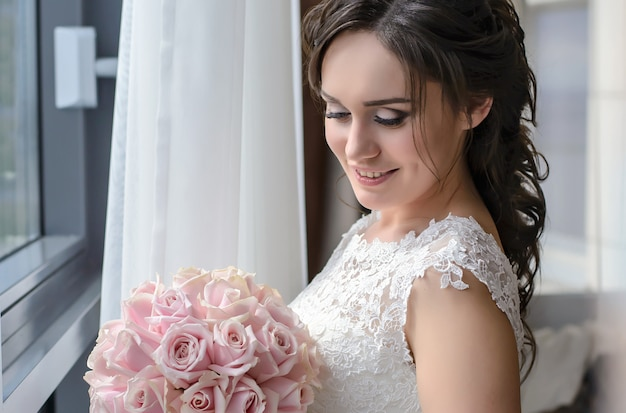 Charmante bruid bij het raam met een bruiloft boeket