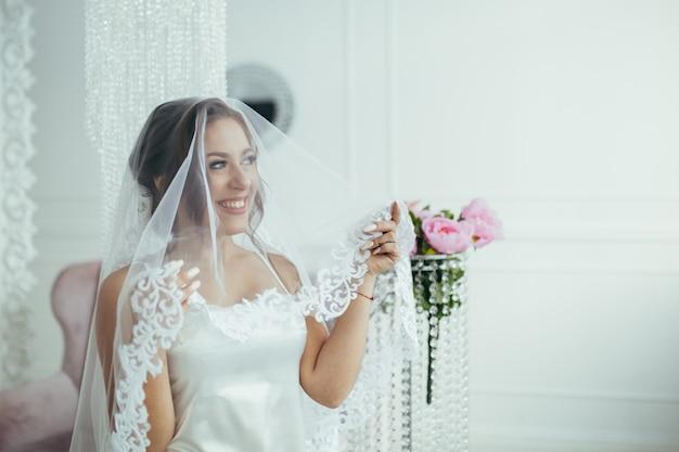 Charmante bruid in de ochtend glimlachend onder een sluier