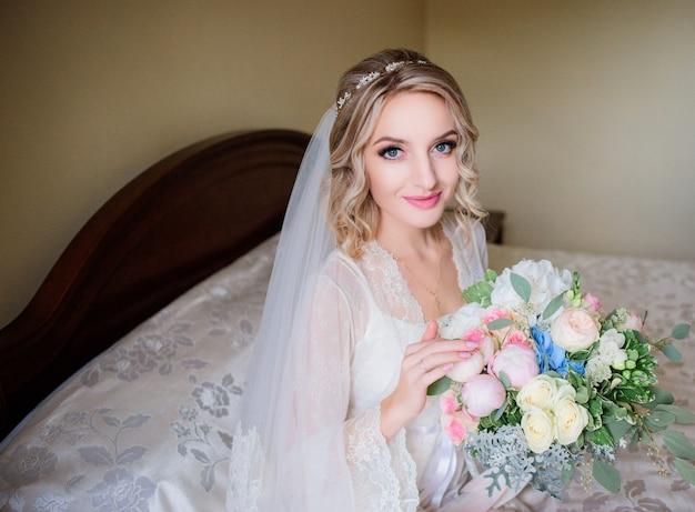 Charmante bruid in een witte robe zit met huwelijksboeket op de tafel