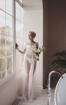 Charmante bruid met trouwbloemen die bij het raam staan