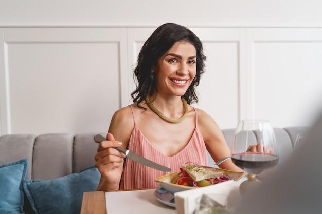 Charmante brunette dame zittend aan tafel met heerlijke frisse salade en glimlachend