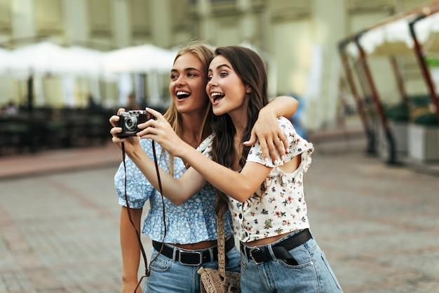 Charmante brunette en blonde vrouwen in stijlvolle bloemenblouses en spijkerbroeken glimlachen en knuffelen buiten