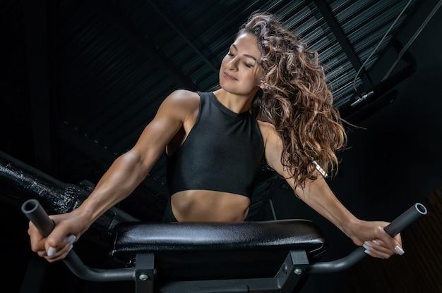Charmante brunette hyperextensie in de sportschool doet. druk op pompen.