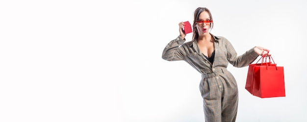 Charmante brunette in glazen poseren in de studio met rode tassen en een doos voor sieraden