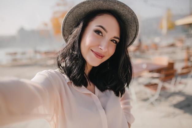 Charmante brunette jonge vrouw positieve emoties uitdrukken tijdens fotoshoot aan kade