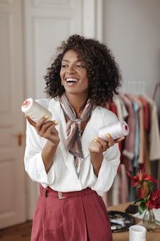Charmante brunette krullende vrouw in witte blouse en bordeauxrode broek lacht, poseert in een gezellige kamer en houdt ballen van draden vast
