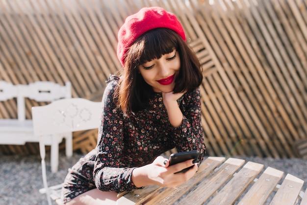 Charmante brunette meisje in vintage pak met telefoon in haar handen zit op terras te wachten op ober om een bestelling te plaatsen. een mooie jonge vrouw in franse outfit kwam naar het openluchtrestaurant voor de lunch.