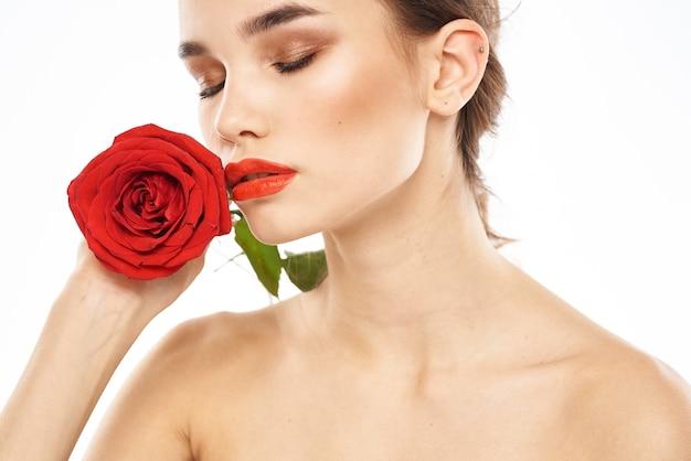 Charmante brunette meisje met make-up op haar gezicht en een rode roos in haar hand.