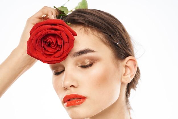 Charmante brunette meisje met make-up op haar gezicht en een rode roos in haar hand