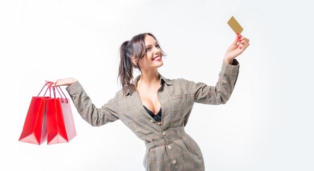 Charmante brunette poseren in de studio met rode pakketten en een bankkaart
