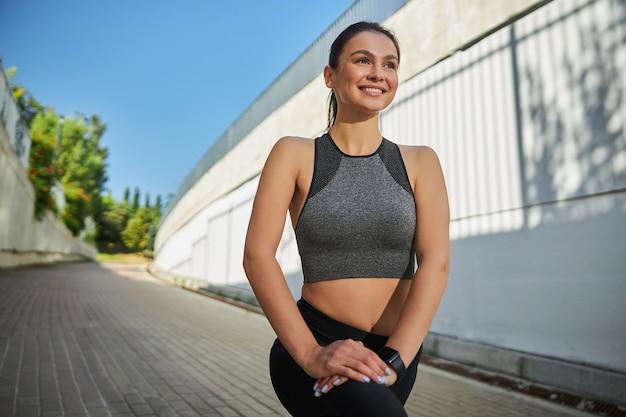 Charmante brunette sportvrouw die haar lichaam fit houdt terwijl ze werkt aan het verlichten van haar spieren