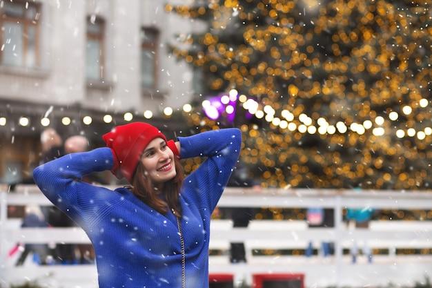 Charmante brunette vrouw die plezier heeft op de kerstmarkt tijdens de sneeuwval. ruimte voor tekst