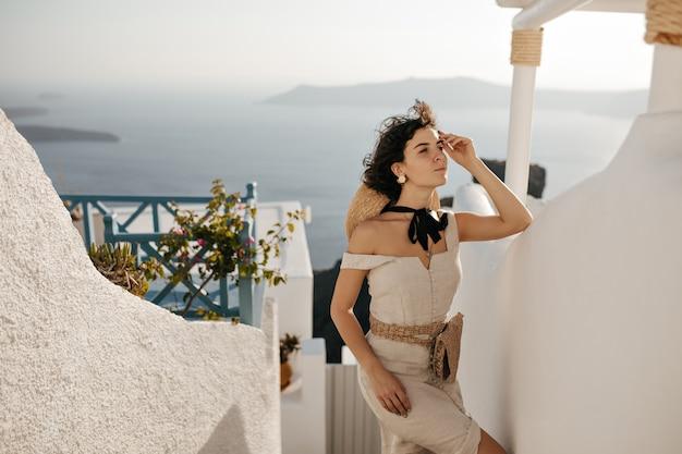 Charmante brunette vrouw in beige zomerjurk met strozak leunt buiten op witte muur wall
