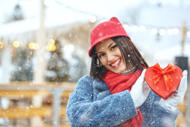 Charmante brunette vrouw in winterjas met een geschenkdoos op kerstmarkt tijdens de sneeuwval. ruimte voor tekst