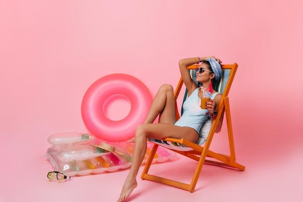 Charmante brunette vrouw sap drinken in ligstoel